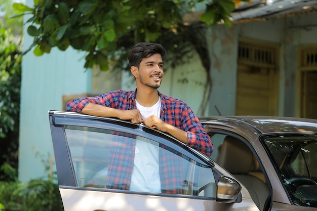 Jeune homme indien avec sa voiture