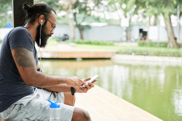 Jeune homme indien sérieux avec la barbe assis à l'étang et utilisant le téléphone tout en écoutant de la musique via l'application