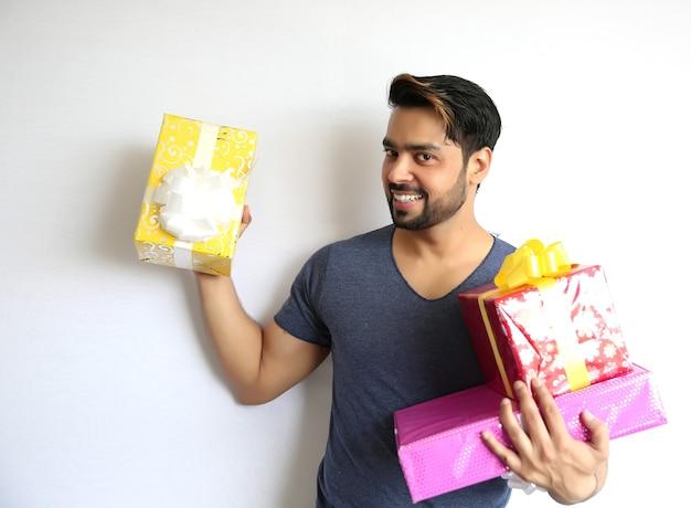 Un jeune homme indien tenant une boîte-cadeau, noël, saint valentin, anniversaire, concept de bonheur