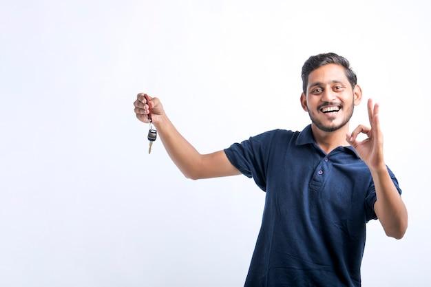 Jeune homme indien tenant la clé en main sur fond blanc.