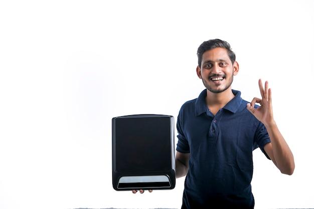 Jeune homme indien tenant une cuisinière électrique à la main sur fond blanc.