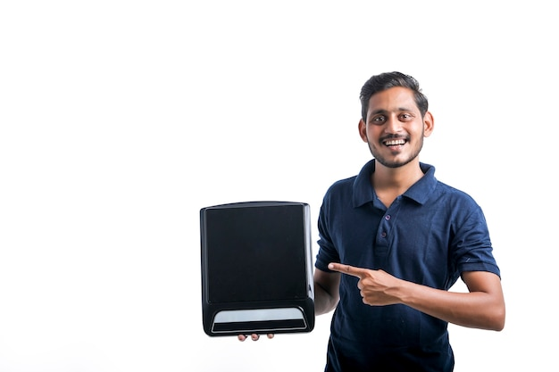 Jeune Homme Indien Tenant Une Cuisinière électrique à La Main Sur Fond Blanc. Photo Premium