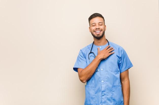 Jeune homme infirmier sud-asiatique éclate de rire en gardant la main sur la poitrine.