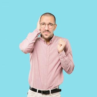 Jeune homme inquiet inquiet des bruits forts et couvrant ses oreilles