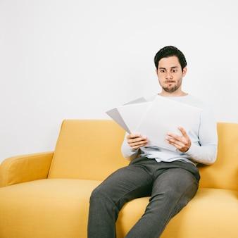 Jeune homme inquiet regardant les papiers
