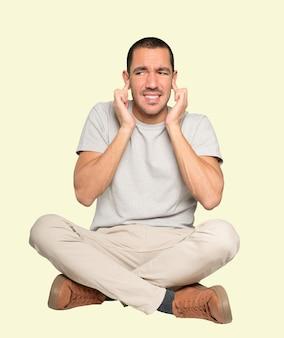 Un jeune homme inquiet s'inquiète des bruits forts et se couvre les oreilles
