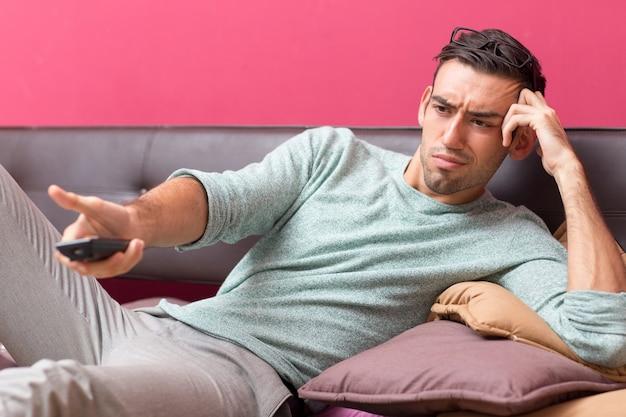 Jeune homme insatisfait change de chaîne de télévision à la maison