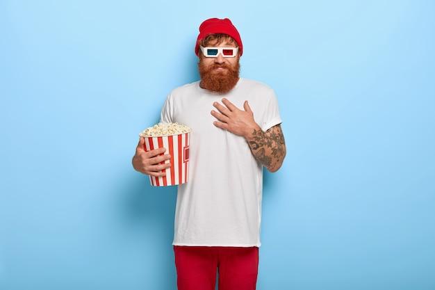 Jeune homme insouciant positif avec barbe au gingembre, touche la poitrine