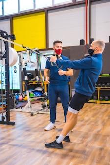 Un jeune homme avec un instructeur dans la salle de sport faisant des exercices de bras dans la pandémie de coronavirus