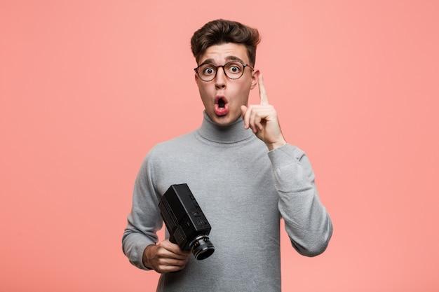Jeune homme intellectuel tenant un appareil photo argentique ayant une excellente idée, concept de créativité.