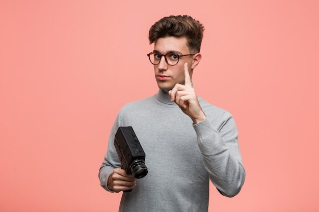 Jeune homme intellectuel tenant un appareil photo argentique montrant le numéro un avec le doigt.