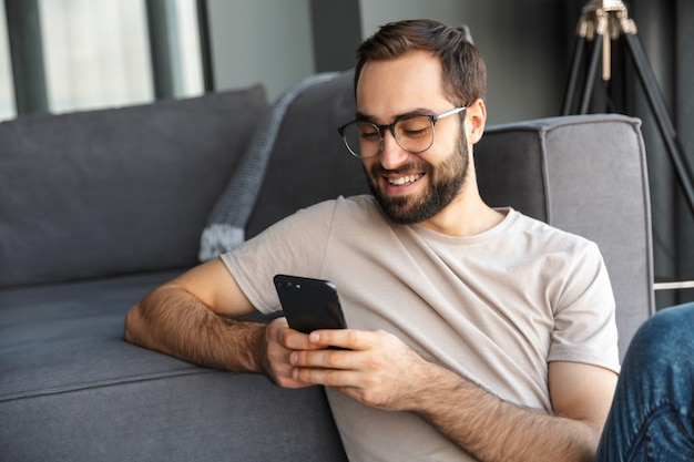 Jeune homme intelligent attirant s'asseyant sur un plancher dans le salon, utilisant le téléphone portable