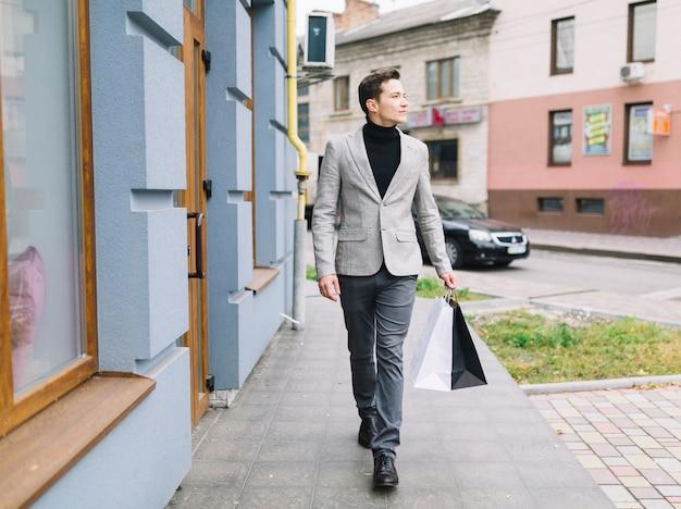 Un jeune homme intelligent, tenant des sacs de shopping, marchant dans la rue