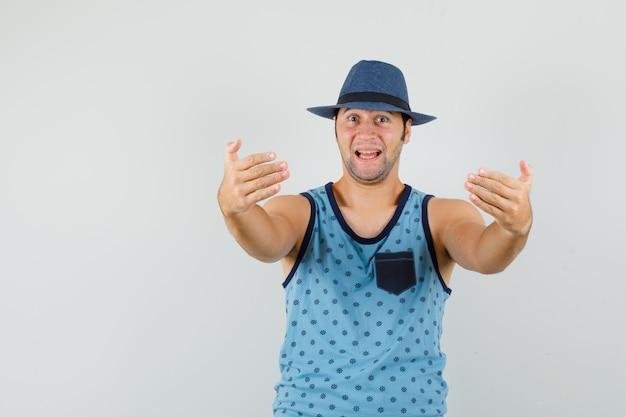 Jeune homme invitant à venir en maillot bleu, chapeau et à l'optimiste.