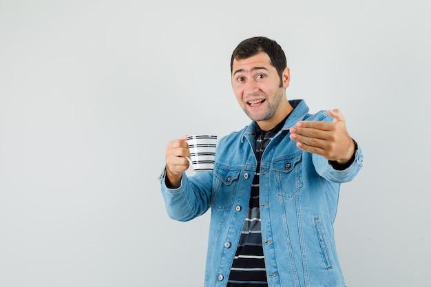 Jeune homme invitant à venir tout en tenant une tasse de boisson en t-shirt, veste et à jolly