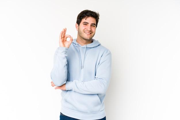 Jeune homme isolé sur blanc fait un clin d'œil et détient un geste correct avec la main.