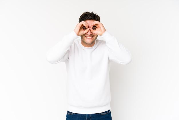 Jeune homme isolé sur blanc montrant un signe correct sur les yeux