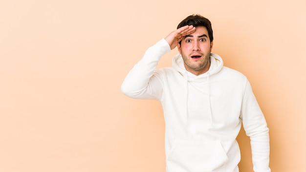 Jeune homme isolé sur un espace beige crie fort, garde les yeux ouverts et les mains tendues.