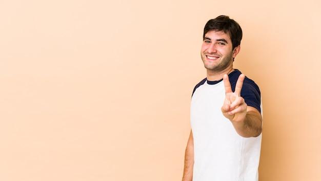 Jeune homme isolé sur un espace beige montrant le signe de la victoire et souriant largement.