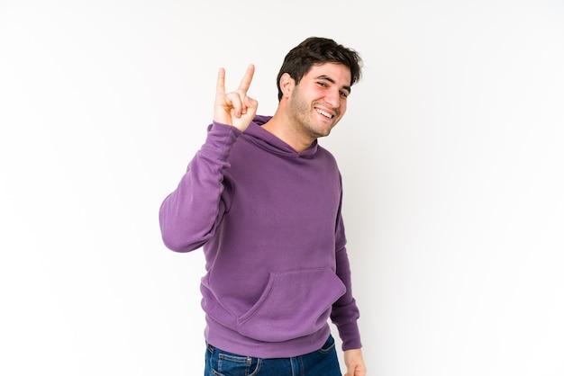 Jeune homme isolé sur un espace blanc montrant un geste de cornes comme un concept de révolution.