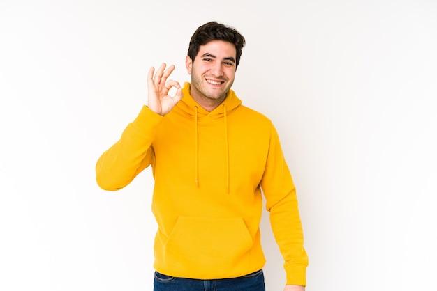 Jeune homme isolé sur fond blanc gai et confiant montrant un geste correct.