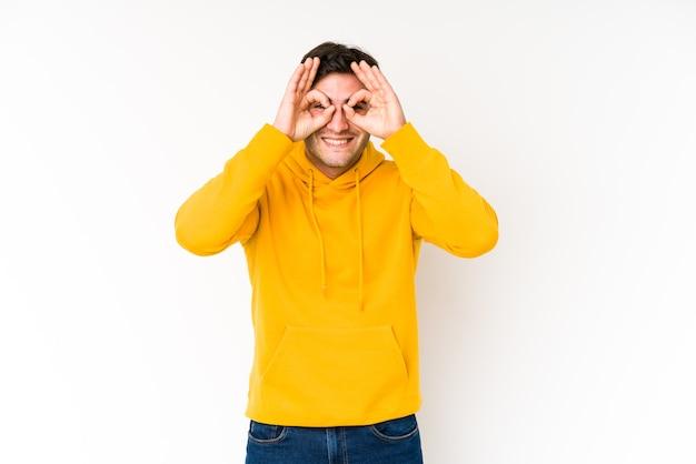Jeune homme isolé sur fond blanc montrant un signe correct sur les yeux