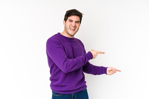 Jeune homme isolé sur fond blanc pointant avec l'index vers un espace de copie, exprimant l'excitation et le désir.