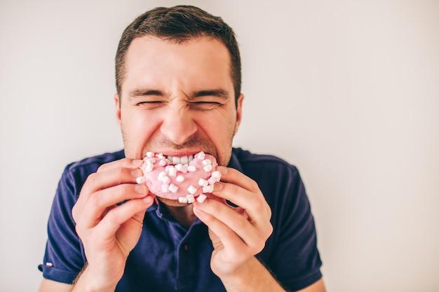 Jeune homme isolé sur fond. guy mord la pièce de beignet rose avec plaisir.