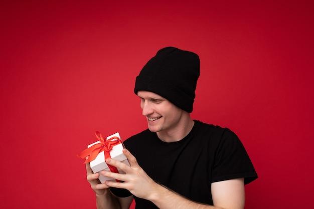 Jeune homme isolé sur fond rouge mur portant un chapeau noir et noir t