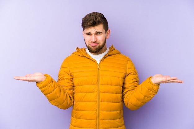 Jeune homme isolé sur fond violet confus et douteux en haussant les épaules pour tenir un espace de copie.