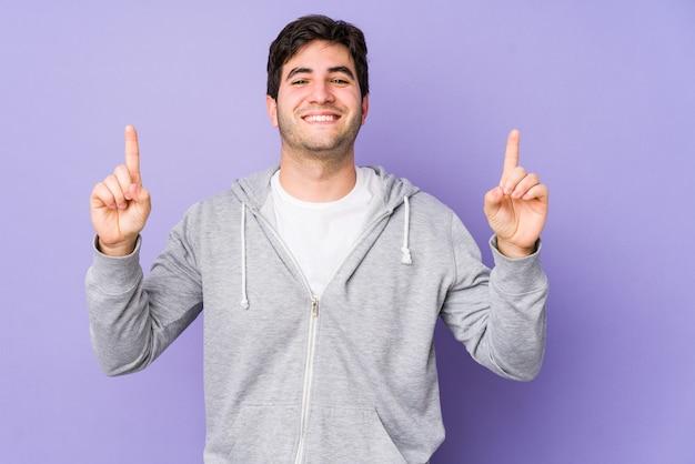 Jeune homme isolé sur fond violet indique avec les deux doigts avant montrant un espace vide.
