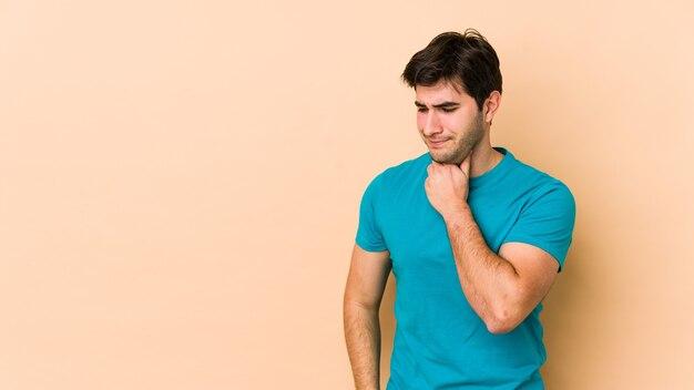 Jeune homme isolé sur un mur beige souffre de douleurs dans la gorge en raison d'un virus ou d'une infection