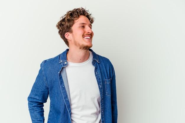 Jeune homme isolé sur un mur blanc détendu et heureux rire, cou tendu montrant les dents