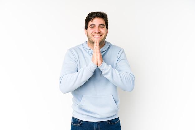 Jeune homme isolé sur un mur blanc, main dans la main en priant près de la bouche, se sent confiant.