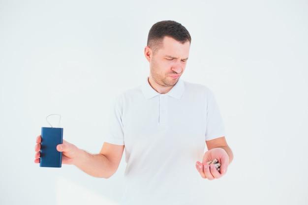 Jeune homme isolé sur mur blanc. malheureux homme tenant des piles et une banque d'alimentation dans les mains et les regardant. temps de recyclage pour un style de vie sans gaspillage.