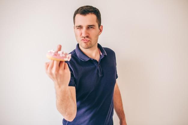 Jeune homme isolé sur mur blanc. rude guy show baise avec le doigt. donut dessus. délicieux repas délicieux mais malsain.