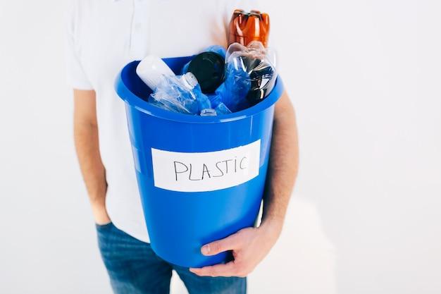 Jeune homme isolé sur mur blanc. vue en coupe d'un gars tenant un seau bleu avec du plastique à l'intérieur. temps de recyclage pour un style de vie sans gaspillage. bon pour l'environnement.