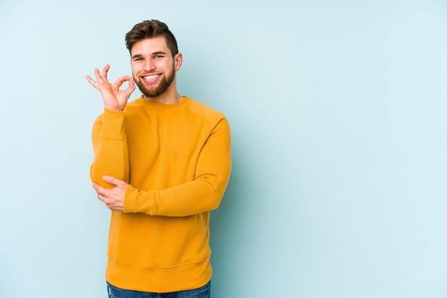 Jeune homme isolé sur le mur bleu fait un clin d'œil et détient un geste correct avec la main