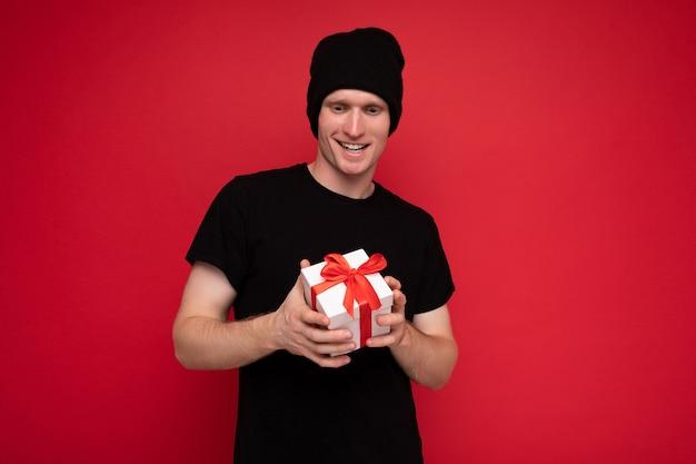 Jeune homme isolé sur mur de fond rouge portant un chapeau noir et un t-shirt noir tenant une boîte cadeau blanche avec un ruban rouge et regardant la caméra.