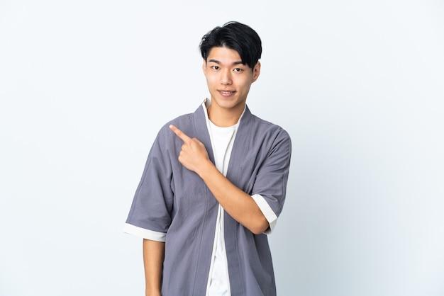 Jeune homme isolé pointant vers le côté pour présenter un produit