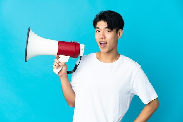 Jeune homme isolé tenant un mégaphone et souriant