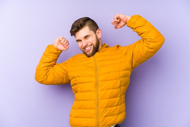 Jeune homme isolé sur violet célébrant une journée spéciale, saute et lève les bras avec énergie.