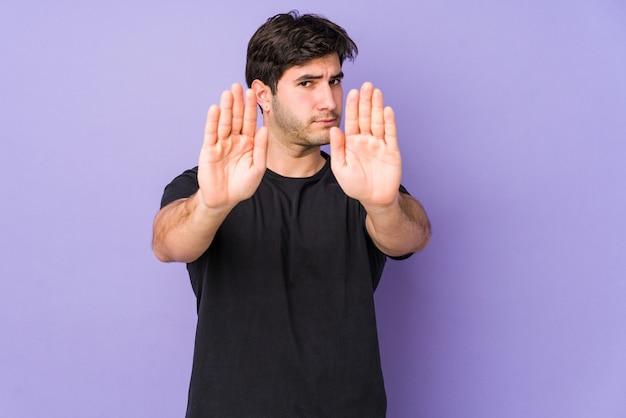 Jeune homme isolé sur violet debout avec la main tendue montrant le panneau d'arrêt, vous prévontant.