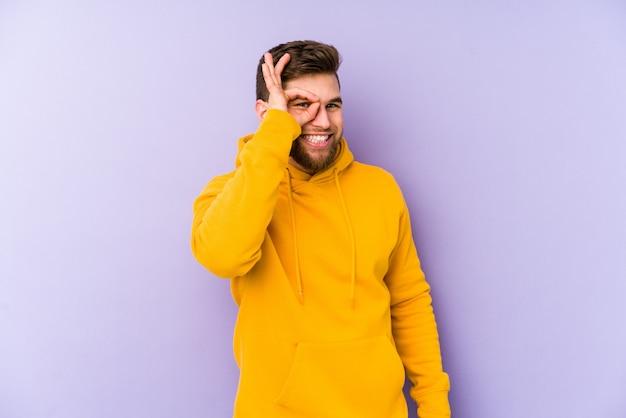 Jeune homme isolé sur violet excité en gardant le geste ok sur les yeux.