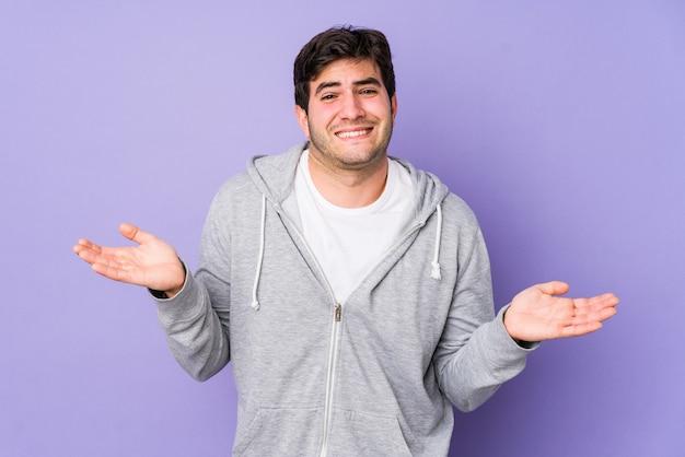 Jeune homme isolé sur violet haussant les épaules confus et douteux pour tenir un espace de copie.