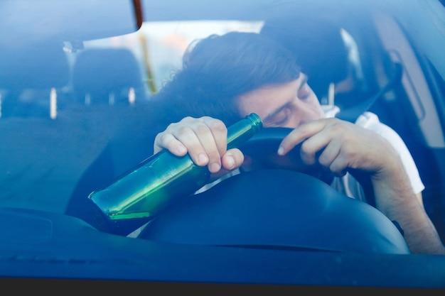 Jeune homme ivre conduisant une voiture avec une bouteille de bière