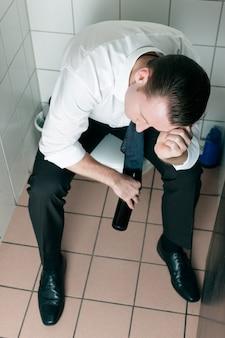 Jeune homme ivre endormi sur la toilette