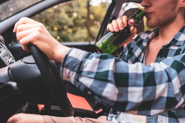 Jeune homme ivre fou conduisant la voiture et buvant de l'alcool