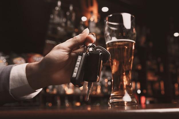 Jeune homme ivre avec un verre de bière et clé dans sa main