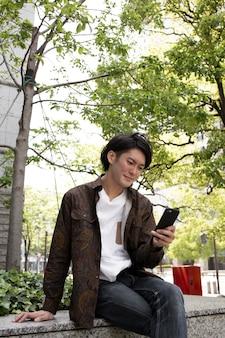 Jeune homme japonais passant du temps seul à l'extérieur
